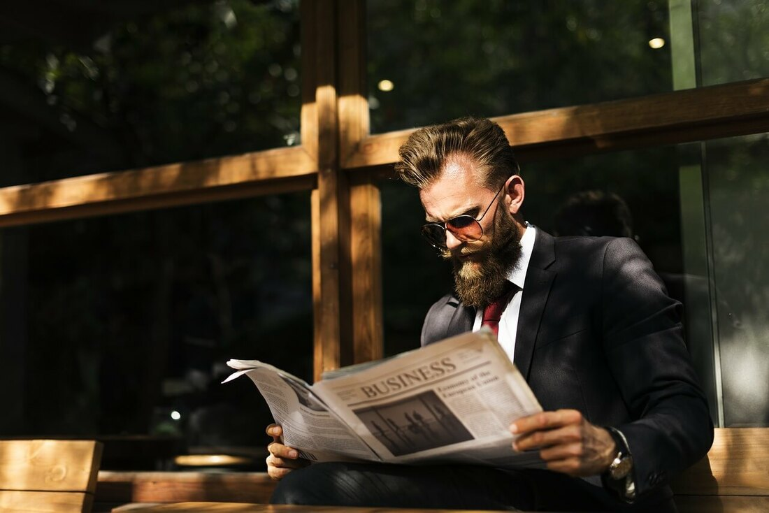 Man reading newspaper - because using the newspaper is a great financial advisor marketing idea